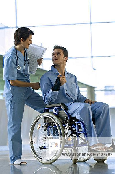 Ein Patient sitzt im Rollstuhl und schaut auf eine hinter ihm stehende Ärztin.