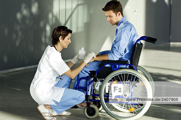 Ärztin beim Auftragen von Medikamenten auf die Hand eines Patienten