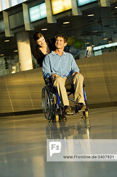 Junge Frau  die einen männlichen Patienten im Rollstuhl schiebt.