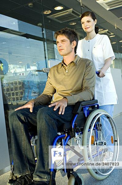 Ärztin schiebt einen männlichen Patienten im Rollstuhl