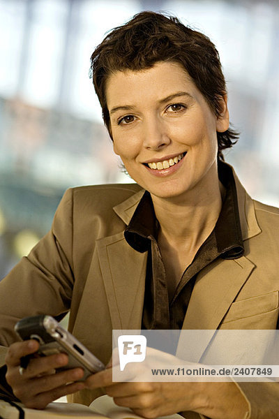 Portrait of a businesswoman operating a mobile phone and smiling