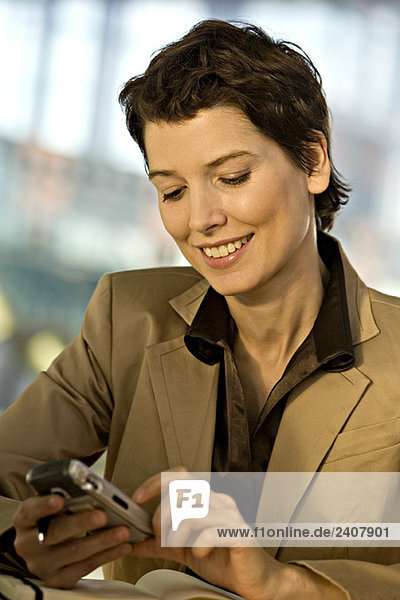 Close-up of a businesswoman operating a mobile phone and smiling