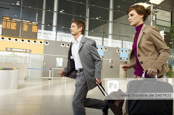 Ein Geschäftsmann und eine Geschäftsfrau  die mit ihrem Gepäck auf einem Flughafen eilen.