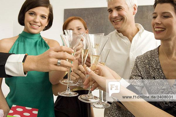 Gruppe von Leuten  die mit Weingläsern auf einer Party anstoßen.