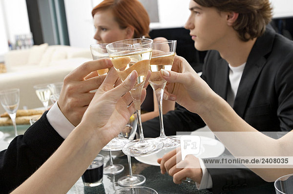 Close-up of human hands toasting with champagne at a dinner party