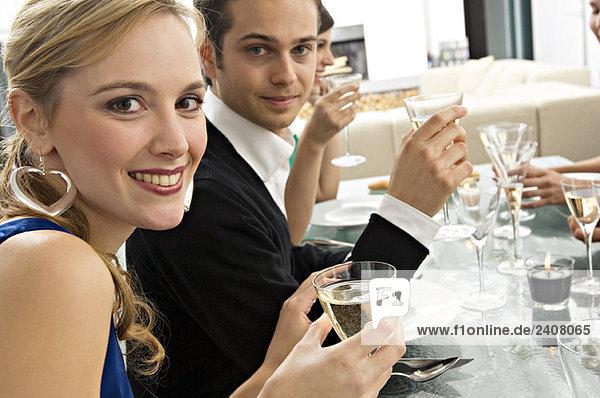 Porträt eines jungen Paares  das bei einer Dinnerparty mit Freunden ein Glas Champagner hält
