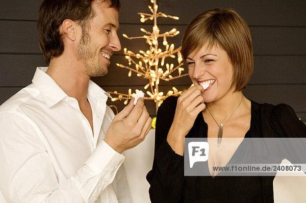 Mittlerer erwachsener Mann und eine junge Frau beim Süßigkeitenessen