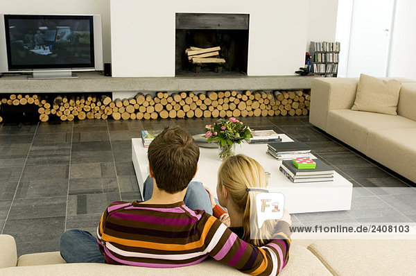 Rückansicht eines jungen Paares  das auf einer Couch sitzt und fernsieht.