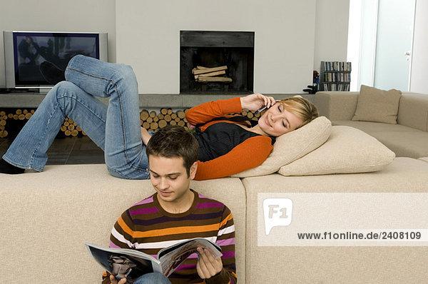 Junger Mann liest eine Zeitschrift mit einer jungen Frau  die ein Handy hinter sich hat.