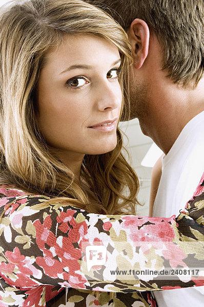 Porträt einer jungen Frau  die einen erwachsenen Mann umarmt.