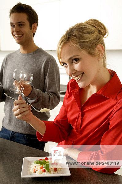 Junge Frau isst Reis mit einer Gabel und ein junger Mann hält Weingläser neben sich.