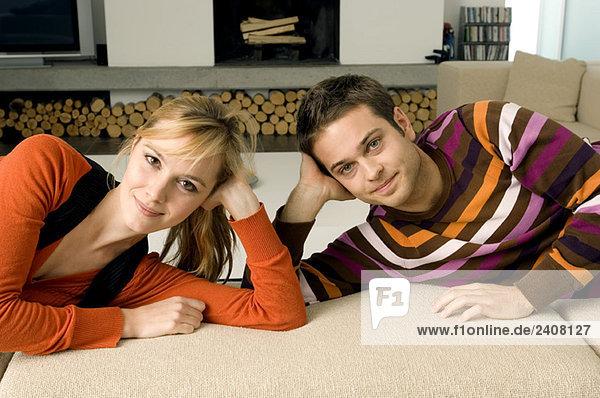 Porträt eines jungen Paares auf einer Couch liegend und lächelnd