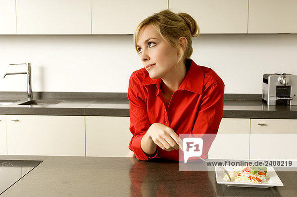 Junge Frau lehnt sich an eine Küchenzeile und denkt nach