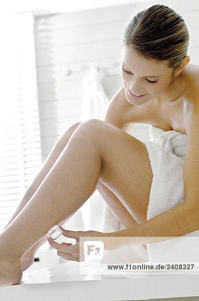 Junge Frau reibt Eiswürfel an ihrem Bein