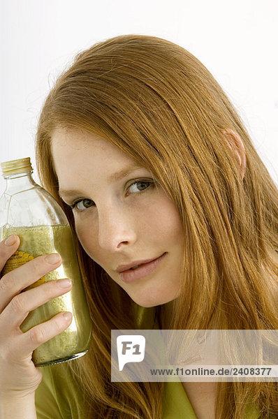 Porträt einer jungen Frau mit einer Flasche Aromatherapieöl