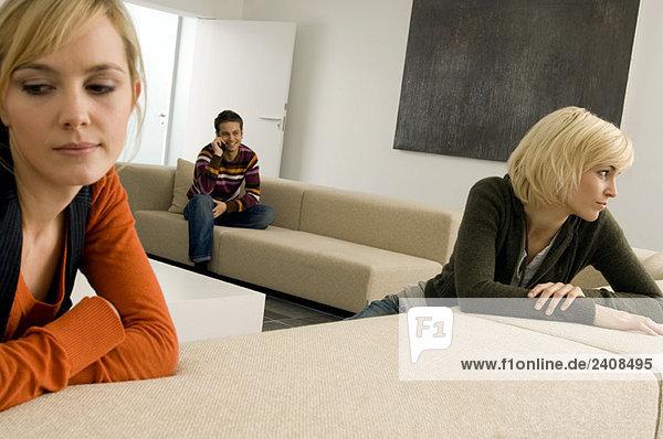 Zwei junge Frauen denken mit einem jungen Mann im Hintergrund.