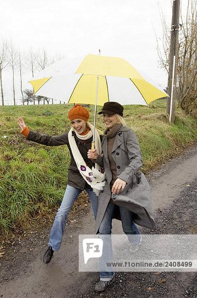 Zwei junge Frauen  die sich unter einem Regenschirm verstecken und auf einem Feldweg spazieren gehen.