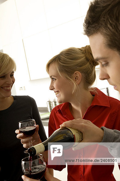 Young man pouring wine into a wine glass with two young women smiling beside him