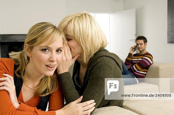 Junge Frau flüstert ihrem Freund mit einem jungen Mann im Hintergrund zu.