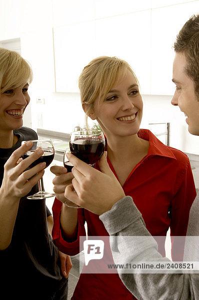 Zwei junge Frauen und ein junger Mann stoßen mit Weingläsern an.