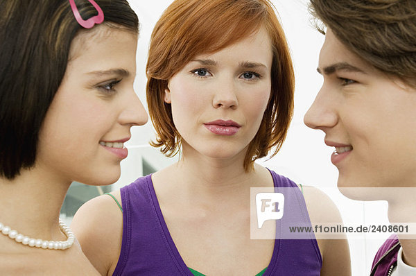 Side profile of a teenage boy smiling with two young women