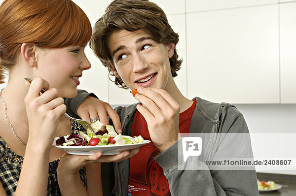 Close-up of a teenage boy and a young woman eating salad
