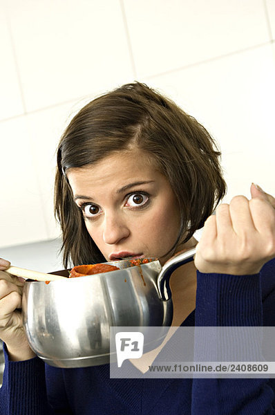 Portrait of a young woman holding a saucepan and looking surprised