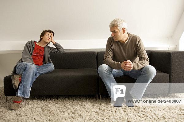 Der reife Mann und sein Sohn sitzen auf einer Couch.