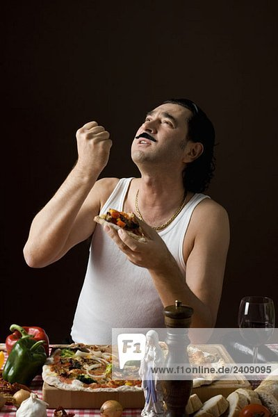 Stereotypical Italian man looking up and gesturing while eating pizza