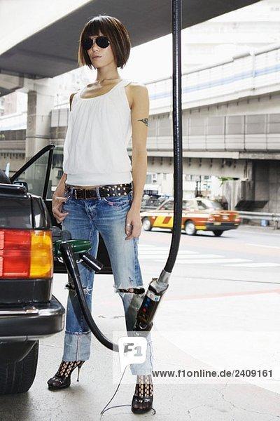 Eine Frau  die ihr Auto auftankt.