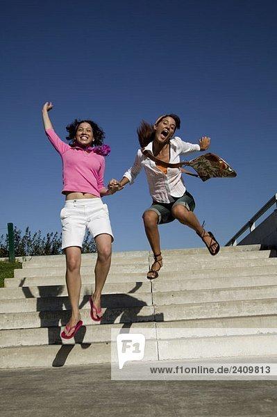 Zwei junge Frauen springen vor Aufregung.