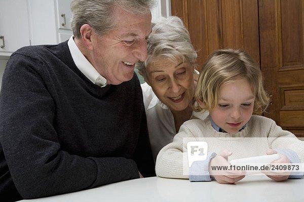 Ein Enkel  der ein elektronisches Gerät benutzt  während seine Großeltern zusehen.