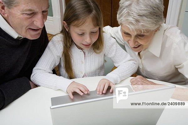 Eine Enkelin  die einen Laptop benutzt  während ihre Großeltern zusehen.
