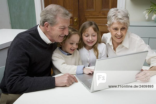 Enkelkinder  die einen Laptop benutzen  während ihre Großeltern zusehen.