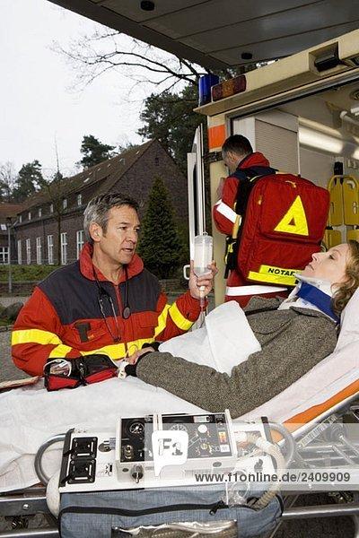 Zwei Sanitäter und ein Patient  der auf einer Krankentrage liegt.