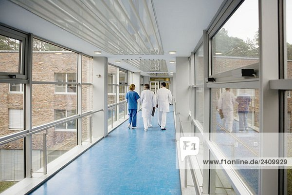 Drei Mitarbeiter des Gesundheitswesens gehen einen Korridor entlang.