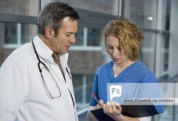 Zwei Gesundheitshelfer sprechen in einem Krankenhauskorridor