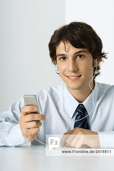 Young man listening to MP3 player  smiling at camera