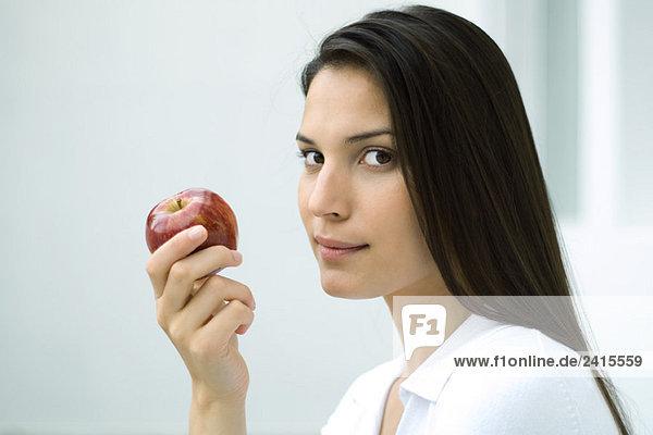 Frau hält Apfel  schaut seitwärts in die Kamera