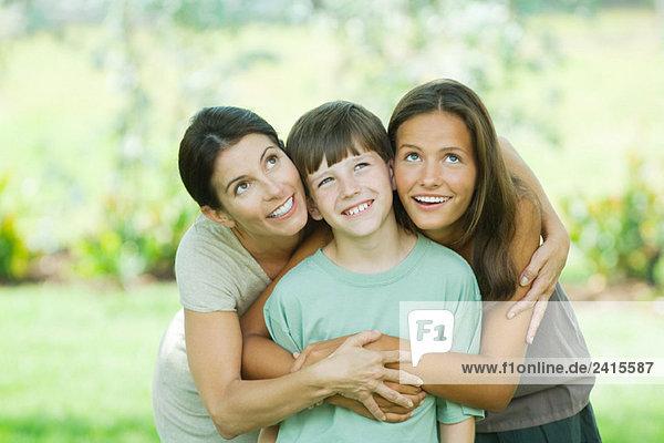 Mutter umarmt Sohn und jugendliche Tochter  alle lächelnd und aufblickend
