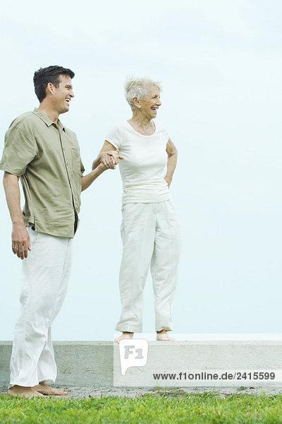 Seniorin auf dem Sims stehend  hält die Hand des erwachsenen Sohnes  beide schauen weg  lächelnd