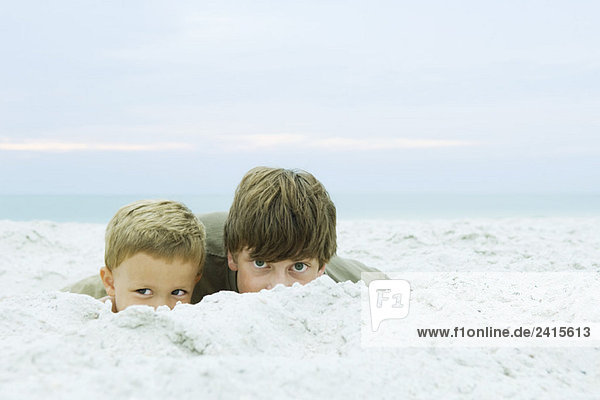 Teen boy and little brother at the beach  peeking over sand at camera