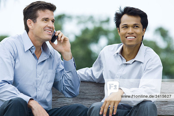 Two men sitting on bench  smiling  one using cell phone