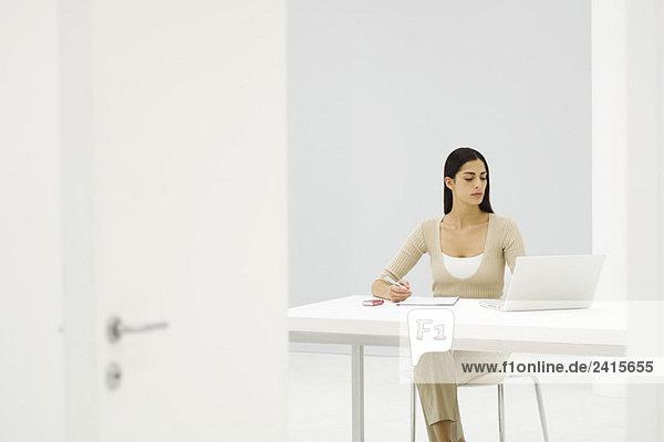 Büroangestellte  die am Schreibtisch sitzt und einen Laptop benutzt