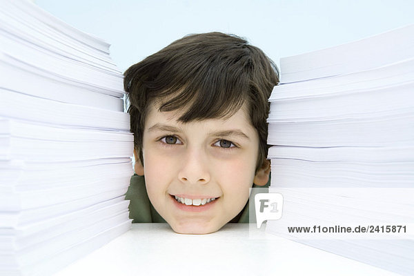 Boy smiling at camera between stacks of paper  portrait