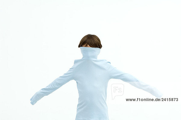 Boy wearing turtleneck pulled over his face  arms outstretched