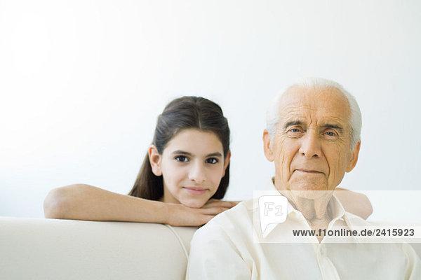 Älterer Mann lächelt in die Kamera  die Enkelin schaut ihm über die Schulter.