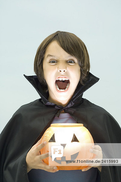 Junge hält Jack o' Laterne  schaut in die Kamera  offener Mund  Portrait
