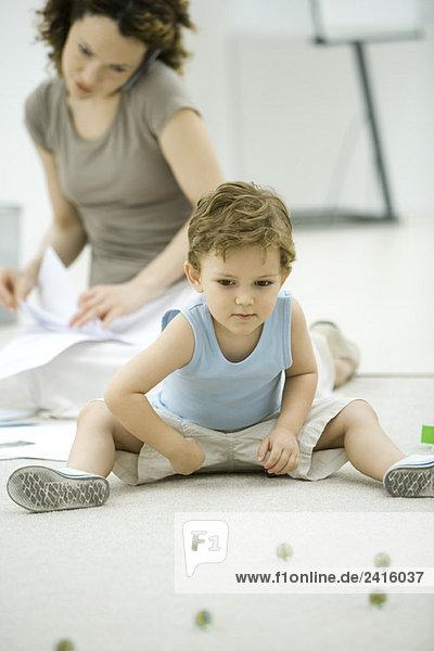 Junge spielt mit Murmeln  während die junge Mutter das Telefon benutzt und sich den Papierkram im Hintergrund ansieht.