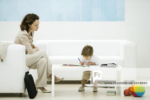 Junge berufstätige Frau mit Aktentasche im Wartezimmer sitzend  während Sohn Farben